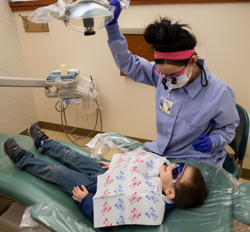 LCCC dental hygiene student Torrey Anaya examines Guadalupe Montoya during this year's Give Kids a Smile event.